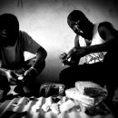 Two Nigerians affiliated with a Guinean drug ring prepare capsules containing cocaine that will be swallowed and then smuggled into Europe.